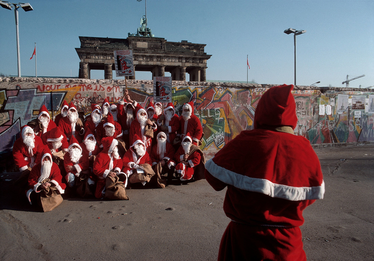 Bruno Barbey GERMANY. West Berlin. Santa Clauses pose for a group photo by the Berlin Wall. 1989.