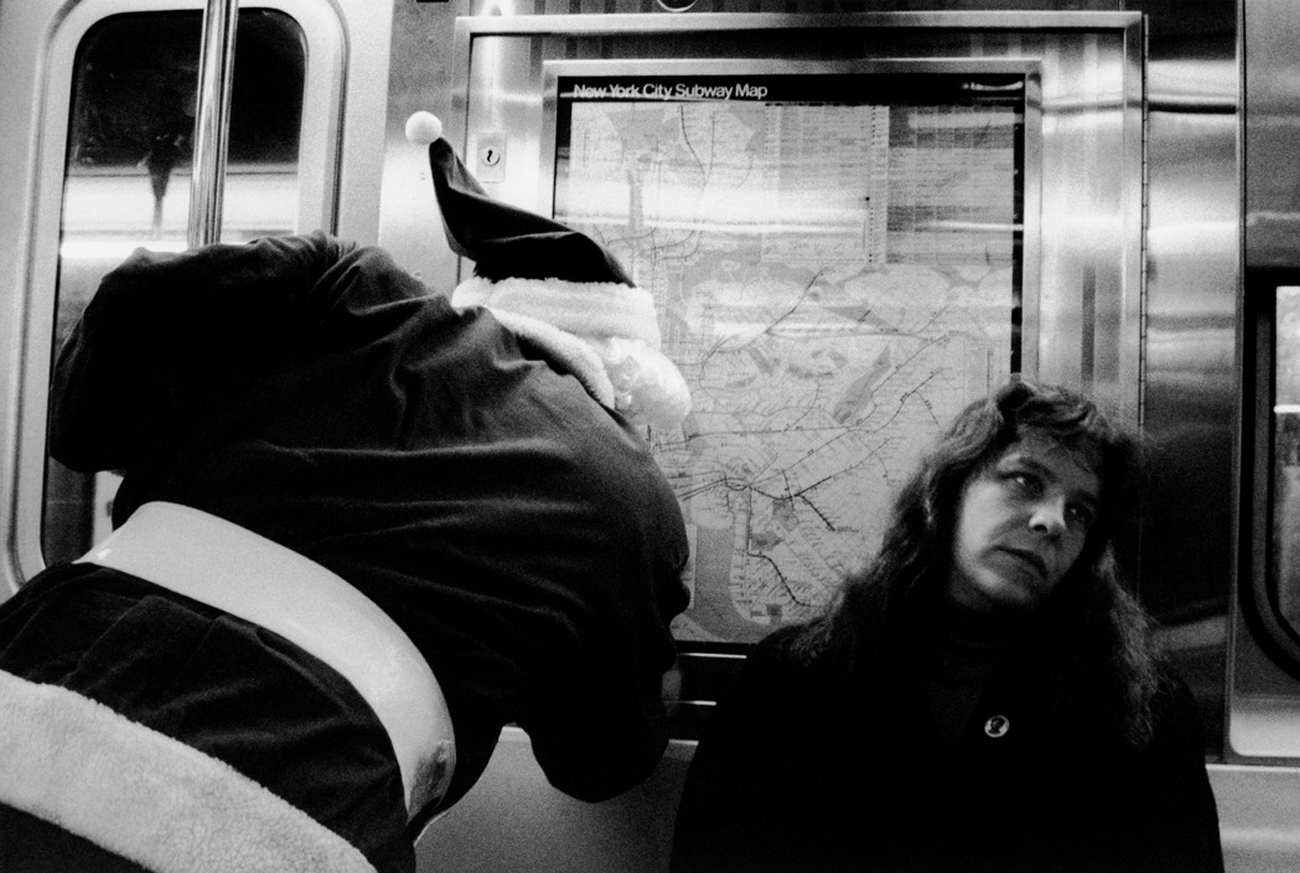Erich Hartmann USA. New York City. 1990. Santa Claus consulting map in subway.